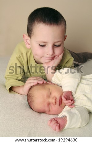 dreaming newborn baby and 5 years old brother - stock photo