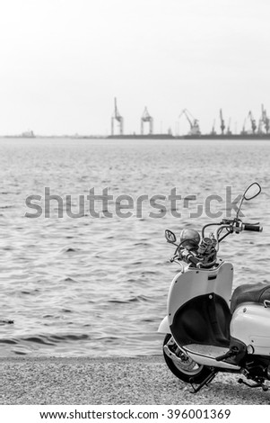 Dreaming of a distant travel. A motorcycle on the sea shore directed towards the water and the horizon. Few loading cranes out of focus in the distance. A black and white photo. - stock photo