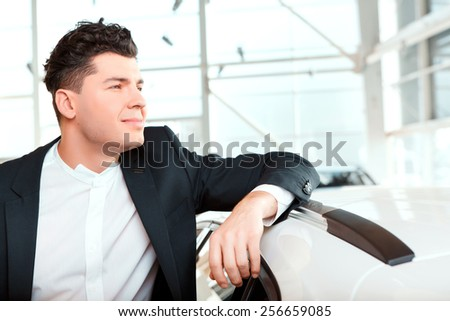 Dreaming of a new car. Smiling handsome man in formalwear leaning at the new car and looking away in car dealership  - stock photo