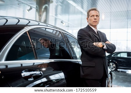 Dreaming of a new car. Thoughtful grey hair man in formalwear leaning at the car and looking away - stock photo