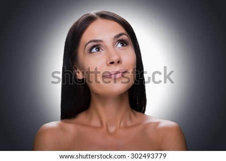Dreaming of? Portrait of thoughtful young shirtless woman looking up and smiling while standing against grey background - stock photo