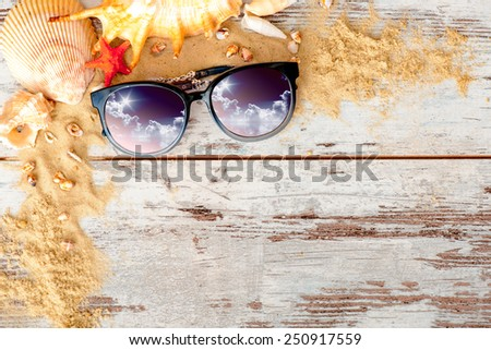 Dreaming of summer. Marine frame in summer vacation concept with sand and sea shells surrounding eyeglasses with sunny sky reflection placed on wooden surface - stock photo
