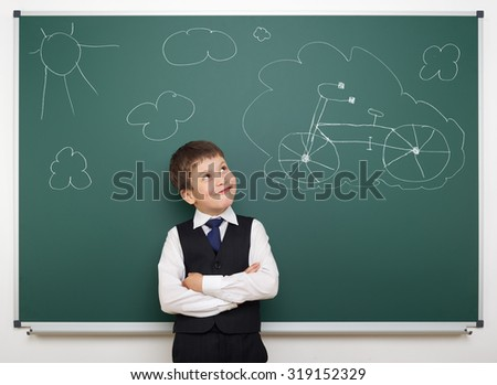 dreaming school boy with painted bicycle on board - stock photo
