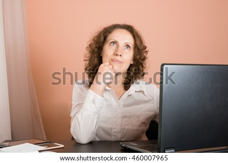 Dreaming smiling happy woman sitting at a laptop