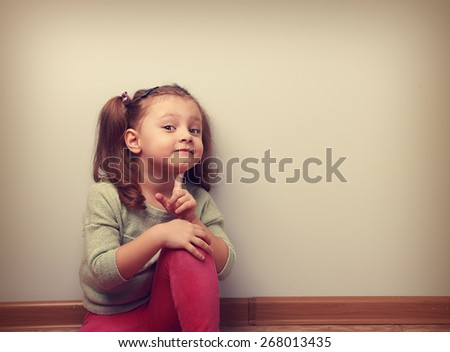 Dreaming smiling sitting kid girl looking fun with finger near face with empty copy space on the wall. Vintage concept portrait - stock photo