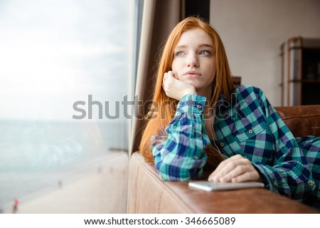 Dreaming thoughtful lovely cute girl with long red hair in checkered shirt looking out of the window and listening to music - stock photo