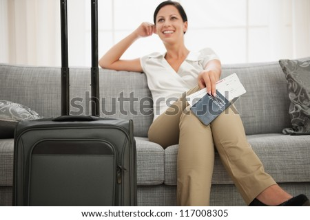 Dreaming woman with passport and air ticket sitting on couch - stock photo