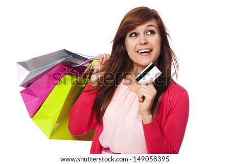 Dreaming woman with shopping bags and credit card  - stock photo
