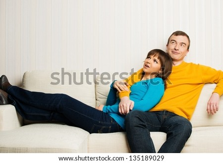 Dreaming young couple on sofa in home interior - stock photo