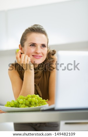Dreaming young housewife eating grape in kitchen - stock photo