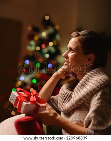 Dreaming young woman sitting chair with Christmas present box - stock photo