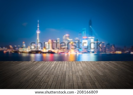 dreamlike city background of shanghai skyline at night with wooden floor as a prospect  - stock photo