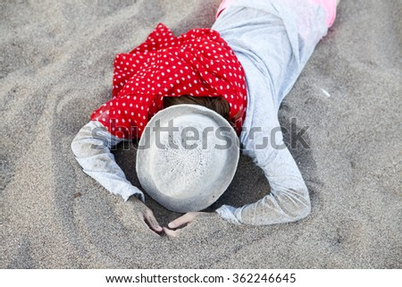 dreams about something else. Girl in grey hat and red scarf lying on the sand.  - stock photo