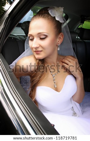 Dreamy beautiful bride sitting in the car - stock photo