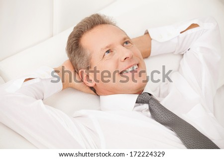 Dreamy businessman. Cheerful grey hair man in shirt and tie lying on bed and smiling  - stock photo