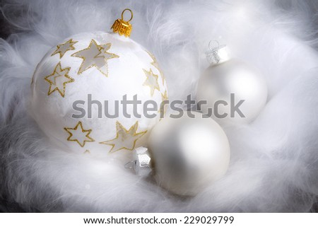Dreamy Christmas arrangement with silver baubles on fluffy white material, high-key studio shot - stock photo