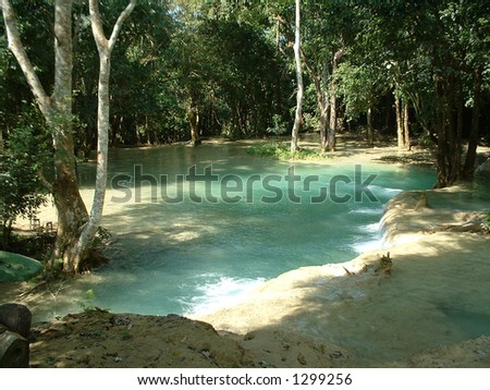 Dreamy emerald waterfall in the jungle, Laos, Southeast Asia - stock photo