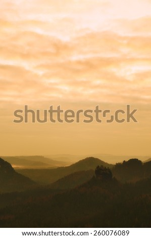 Dreamy fogy landscape, spring orange pink misty sunrise in a beautiful valley of Saxony Switzerland park. Dark sharp hills increased from fog. - stock photo