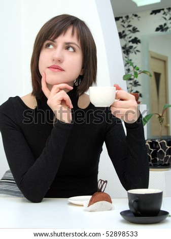 Dreamy girl drinking coffee in a cafe - stock photo