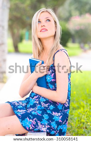 dreamy girl reading a book in a park
