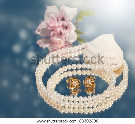 Dreamy image of golden pearl earrings with pearl necklace, seashell and a pale pink flower - stock photo