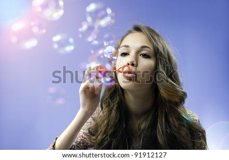Dreamy image of gorgeous young brunette girl blowing colorful soap bubbles. - stock photo
