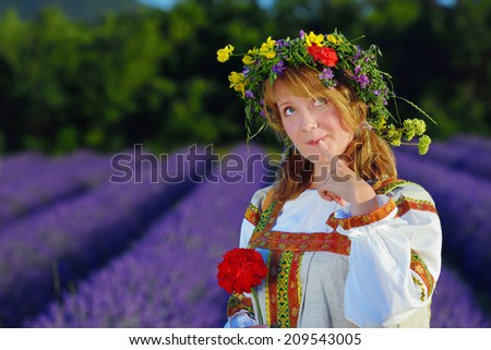 Dreamy peasant girl in a flowers wreath dressed in a russians gown stands in lavender field