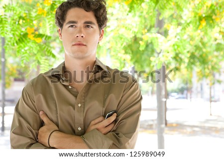 Dreamy portrait of an attractive young businessman with arms crossed, holding a smart phone while standing under green trees in blossom. - stock photo