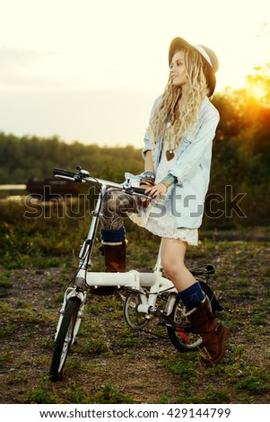 Dreamy smiling girl in boho style clothes rides a bicycle. Beauty, fashion. Summertime, sunset. - stock photo