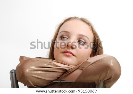 Dreamy teenage girl is putting her head on the folded hands. She is sitting on the chair and looking sideways. - stock photo