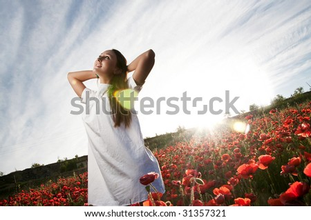 Dreamy woman in poppy flowers - stock photo