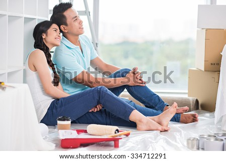 Dreamy young Vietnamese family sitting on the floor of their new apartment - stock photo