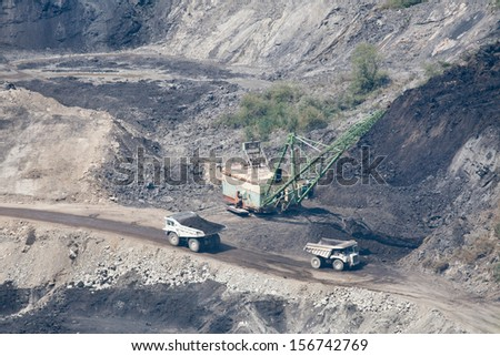 Dredger loading truck with stone from large quarry - stock photo
