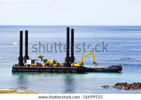 Dredger near the shore cleaning the bay - stock photo