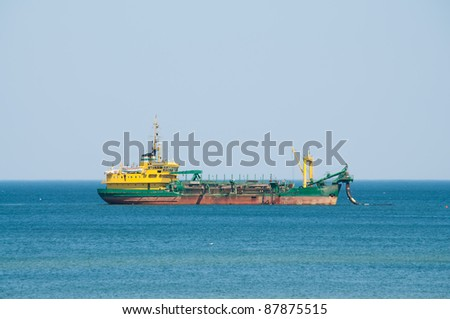 dredger ship working at sea - stock photo