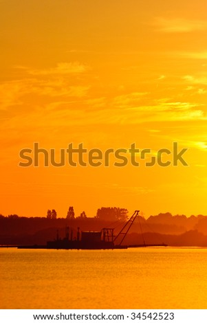 Dredger vessel working in the early morning at sunset - stock photo
