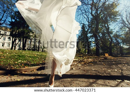Dres hides a bride while she jumps in the park - stock photo