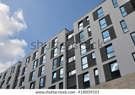 DRESDEN, GERMANY - APRIL 12, 2016: White facade of a modern apartment building with  windows and different black accents on a background of blue sky with clouds. Dresden, Germany. - stock photo