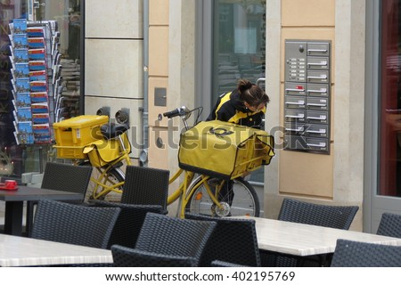 DRESDEN, GERMANY - CIRCA MARCH 2016: postwoman delivering mail in the city centre with her bicycle - stock photo