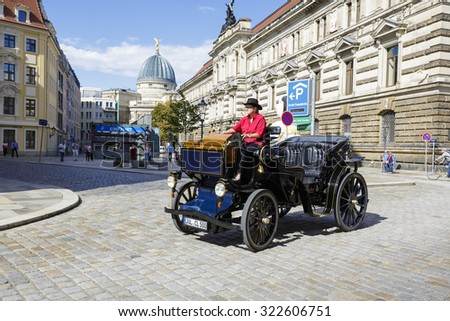 DRESDEN, GERMANY - SEPTEMBER 19, 2015: Unrecognized model of the old-fashioned car is run by a lady driver, who usually she takes tourists for sightseeing tours through the streets of city - stock photo