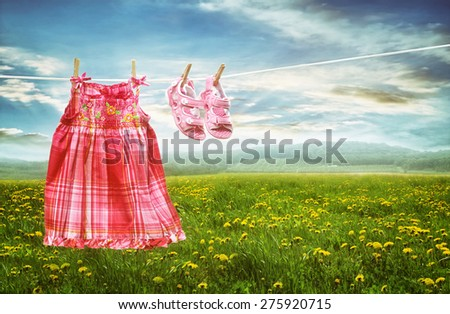 Dress and sandals on clothesline in summer fields of dandelions - stock photo