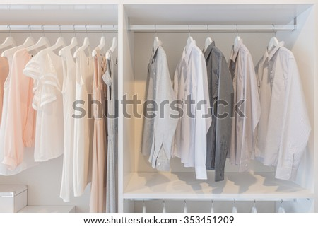 dress and shirts hanging on rail in white wardrobe - stock photo