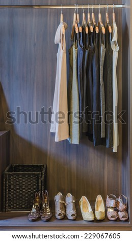 dress and shoes in wooden wardrobe at home - stock photo