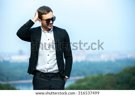 Dress code wearing man is smiling and scratching his head. Skyline in background. Happy young man.