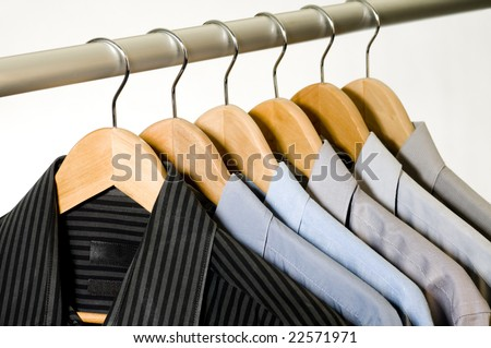 Dress shirts on wooden hangers. - stock photo