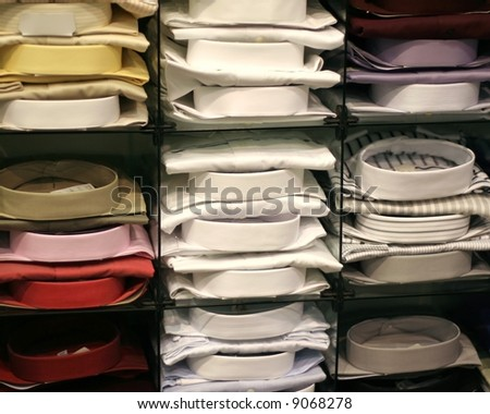 Dress Shirts Stacked on Shelves in a Men's Wear Store - stock photo