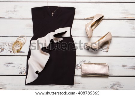Dress with necklace and bracelets. Bracelets and dress on shelf. Female apparel with precious bracelets. Summer evening outfit from catalog. - stock photo