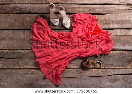 Dress with shoes and bracelets. Lady's outfit on brown table. Aged shelf with stylish outfit. Clothing on aged wooden background. - stock photo