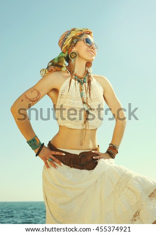 Dressed in boho chic style woman portrait, sunny  outdoor photo against sea. Headband, white lace tank top and skirt, leather belt waist and handmade boho jewelry - stock photo