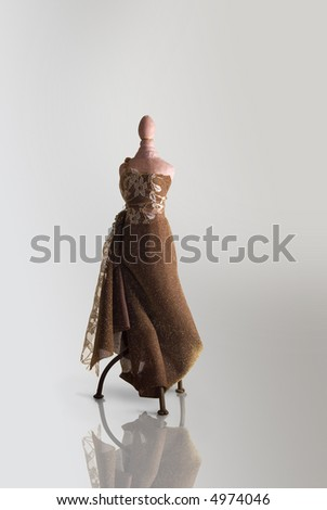 dressed table top mannequin over gray background - stock photo